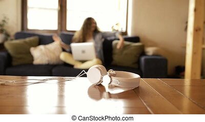 Headphones laid on table. Teenage girl listening music, dancing.