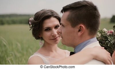 Close-up of a beautiful bride. She hugs her groom and...