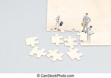 businessmen collaborate holding up jigsaw puzzle pieces