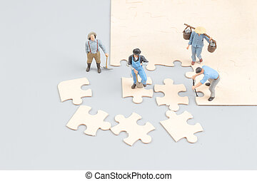 people collaborate holding up jigsaw puzzle pieces