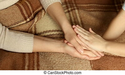 The child gently strokes my mother's hands - Hands of the...