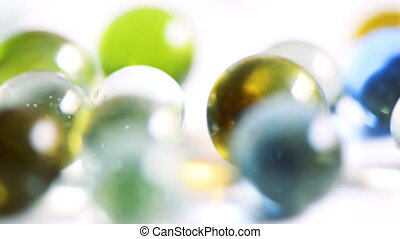Colorful rolling glass marbles on white background.