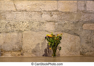 flowers in front of a stone wall, a symbol of decoration,...