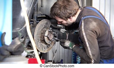man repairing old rusty car brake system. Service care customer safety.