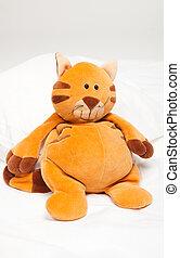 Toy cat - Toy orange cat sitting on white blanket