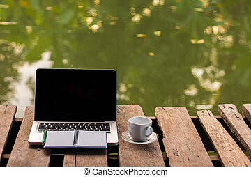 Laptop with coffee cup on the wood. background green