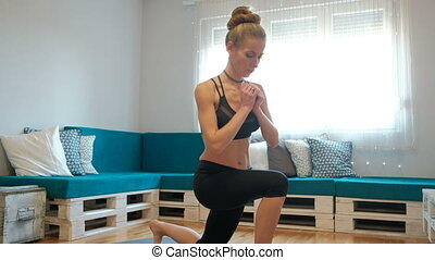 A young woman at home makes stretching the muscles of her...