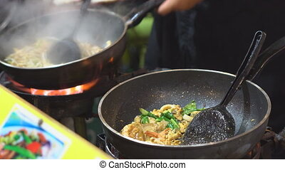 Chef cooking Pad Thai stir-fried rice noodles with shrimp