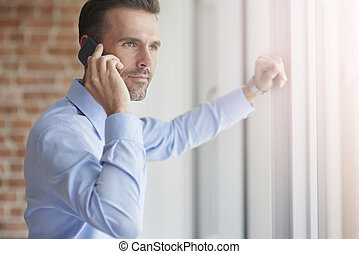 Businessman with phone leaning on the window