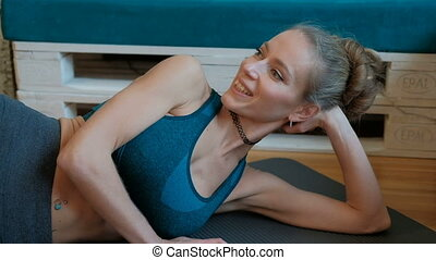Smiling woman work-out lying on floor indoors. Laughing...