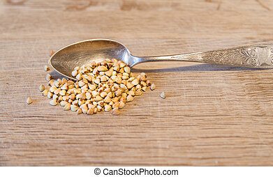 Silver spoon with buckwheat on a wooden board