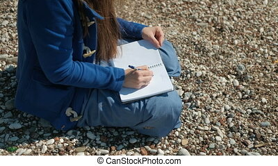 A woman is sitting on a stony beach and writing a pen in the notebook.