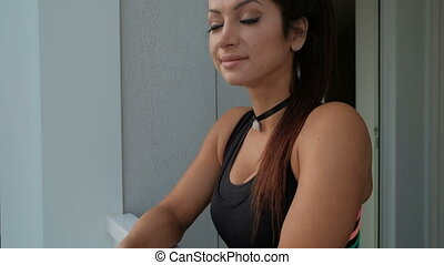 Smiling woman in sports clothes standing balcony in...