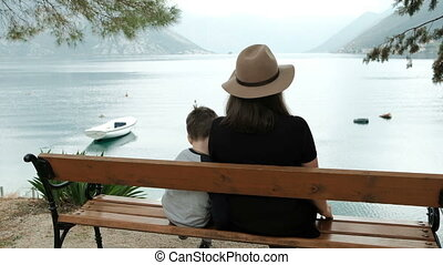 Mom and son sitting on a bench by the lake and look at the mountains.