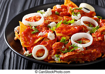 Hot Mexican food chilaquiles with chicken close-up on a...