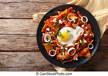 Mexican nachos with tomato salsa, chicken and egg close-up....