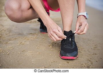 Woman tying a sport shoes
