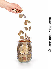 coins falling into the glass jar from womens hand isolated