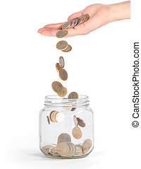 coins falling into the glass jar from hand isolated