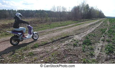 A girl riding a motorbike on a country road