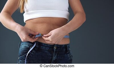 Overweight Female woman measuring her waist with a measuring...