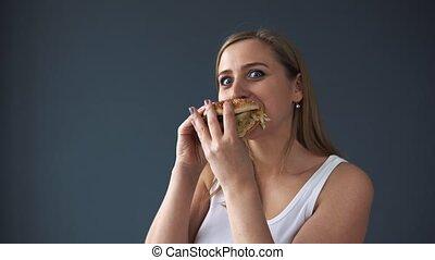 Overweight woman eating hamburger and looking at the camera...