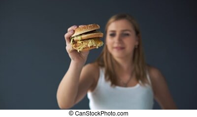 Overweight woman with a hamburger on a gray background. She thinks or eat fast food