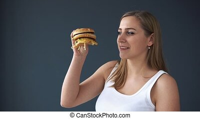 Overweight woman eating hamburger on grey background. The...