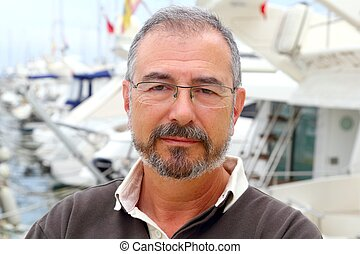 Senior man on marina sport boats portrait