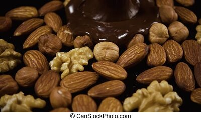 Melted chocolate pours on nuts. Slow motion - Dark melted...