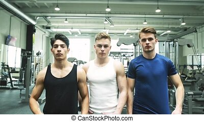 Three young fit men in gym posing. - Three young handsome...