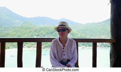 Tanned boy in a hat and glasses sits on the background of the sea and mountains