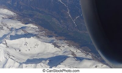 Operating jet engine of the airplane, snowy montain peaks and distant alpine town. 4K video