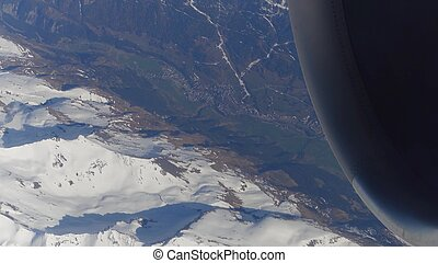 Operating jet engine of the airplane, snowy montain peaks...