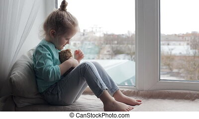 Girl sitting on window sill - Cute girl sitting on window...