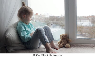 Girl smiling on a window sill - Young girl talking and...