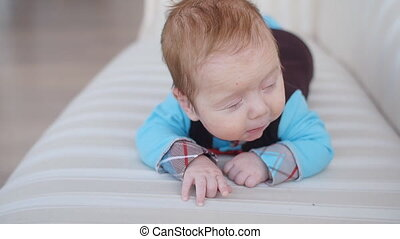 Portrait of cute baby boy lying down on blanket - Portrait...