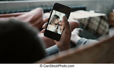 African man uses Smartphone, looks at photos with Caucasian...
