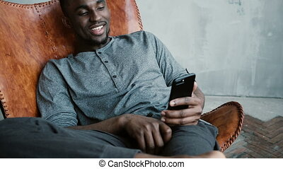 Portrait of African man sitting in chair, using Smartphone....