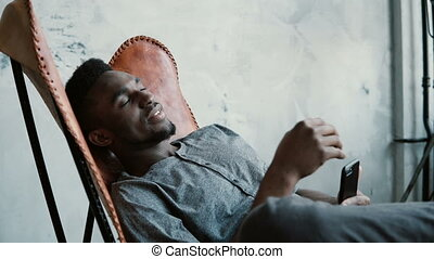 Portrait of young African man in chair. Male is seriously...