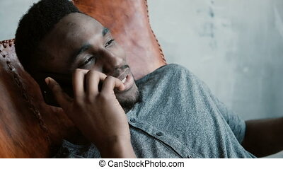 Portrait of young African male with a beard sitting in chair, using his Smartphone. Man talks on phone and smiles.