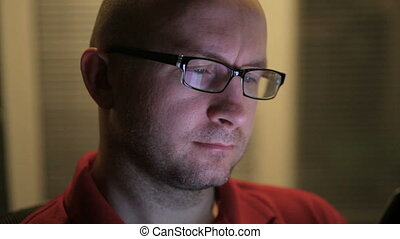 man in glasses sits with a tablet in his hands at the office