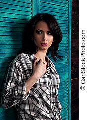 Beautiful makeup woman in trendy black and white checkered shirt looking with fear emotion on wooden background. Short hairstyle. Contrast closeup portrait