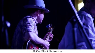 Musician in hat plays guitar in night club, close up,...