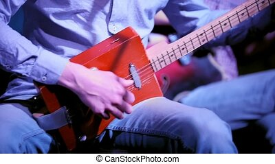 Musician in night club plays guitar made from a cigar box,...