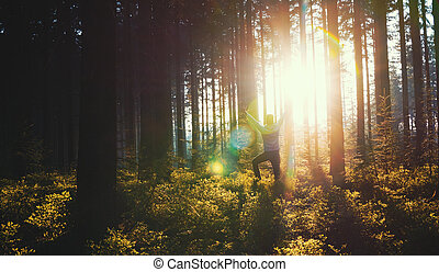 Young man in silent forrest with sunlight