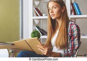Girl using laptop and calculator - Side view of beautiful...