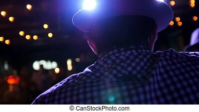 Guitarist at scene in bar - musician in hat plays guitar,...