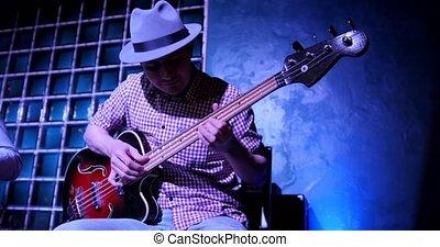 Guitarist at scene in bar - musician in hat plays guitar, ,...