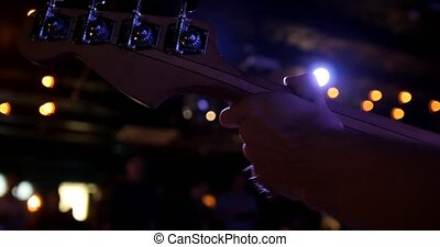 Musician in night club - guitarist holds the guitar soundboard